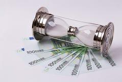 EURO banconote e una clessidra su un fondo bianco Il tempo è denaro concetto Immagine Stock Libera da Diritti