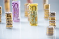 Euro banconote rotolate e torri delle monete impilate in altre posizioni immagini stock