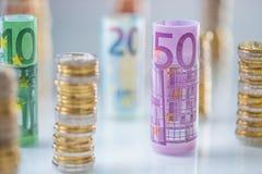 Euro banconote rotolate e torri delle monete impilate in altre posizioni immagini stock libere da diritti