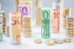 Euro banconote rotolate e torri delle monete impilate in altre posizioni fotografia stock libera da diritti
