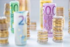 Euro banconote rotolate e torri delle monete impilate in altre posizioni fotografie stock libere da diritti