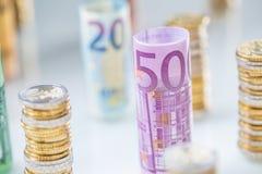 Euro banconote rotolate e torri delle monete impilate in altre posizioni fotografie stock