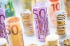 Euro banconote rotolate e torri delle monete impilate in altre posizioni immagine stock libera da diritti