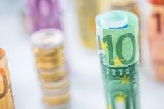Euro banconote rotolate e torri delle monete impilate in altre posizioni fotografia stock