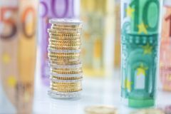 Euro banconote rotolate e torri delle monete impilate in altre posizioni immagine stock
