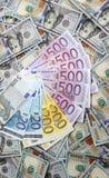 Euro banconote su un fondo di cento banconote del dollaro Fotografia Stock