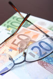 Euro bank note. 20, 50, and 100 euro bank notes with a pair of glasses royalty free stock image