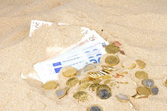Euro bank notes and coins in the sand Stock Image