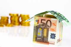Euro bank notes House and coins Stock Images