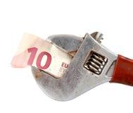 euro bankbiljet 10 op de regelbare moersleutel van de buigtangpijp Stock Foto's