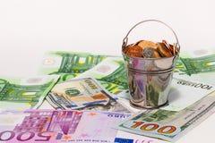 Euro bankbiljetten, dollars en emmer met Russisch geld Stock Foto's