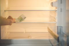 Euro bankbiljetten in een lege ijskast: een handvol van 100 eurobankbiljetten in een lege ijskast De vrouwelijke hand neemt geld  Stock Afbeelding