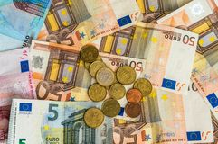 Euro bankbiljetten en euro muntstukken Stock Foto