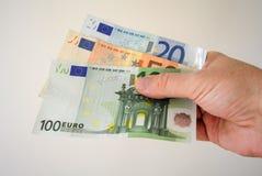 Euro bankbiljetten in witte mensenhand Loonsrekeningen met geld Muntconcept Europese Munt Royalty-vrije Stock Afbeelding