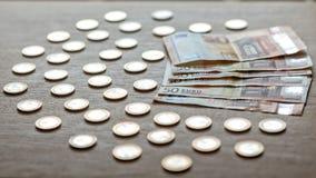 50 euro banknotów i 1 euro monety na lekkim drewnianym tle obraz royalty free