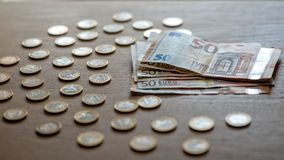 50 euro banknotów i 1 euro monety na lekkim drewnianym tle fotografia stock