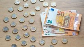 50 euro banknotów i 1 euro monety na lekkim drewnianym tle zdjęcie royalty free