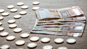 50 euro banknotów i 1 euro monety na lekkim drewnianym tle obrazy royalty free