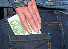 Euro banknote bluejeans. A hand grabbing a 100 Euro banknote in the rear pocket of bluejeans royalty free stock photography