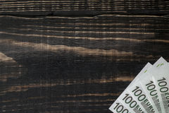 Euro banknote on a dark wooden background. Euro banknote on a dark old wooden background Royalty Free Stock Images