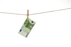 100 Euro banknote hanging on clothesline on white background. Money laundering concept Royalty Free Stock Photos