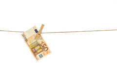 50 Euro banknote hanging on clothesline on white background. Money laundering concept Stock Images