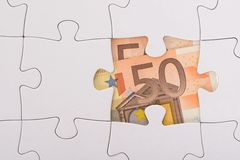 Euro banknote hidden under jigsaw Stock Images