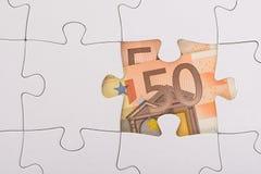 Euro banknote hidden under jigsaw Stock Images