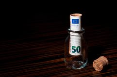 50 Euro Banknote Inside a Bottle. Rolled 50 Euro Banknote Inside a Small Glass Bottle, Saving Money stock photo