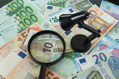 Euro banknote with magnifying glass and lamp as financial tax co Royalty Free Stock Image