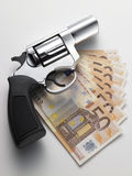 Euro banknote and revolver. On white background Stock Photo