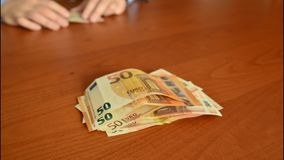 50 euro banknote transfer. Time lapse video of a 50 euro banknote transfer from one side of the table to the other with selective focus on the banknotes stock video footage