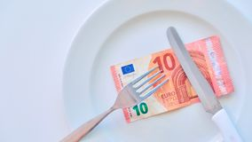 Euro banknote on a white plate, cash in Europe, the cost of lunch in the restaurant.  stock image