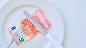 Euro banknote on a white plate, cash in Europe, the cost of lunch in the restaurant.  stock images