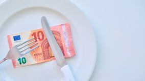 Euro banknote on a white plate, cash in Europe, the cost of lunch in the restaurant.  royalty free stock photography