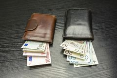 Wallets with Euro and Polish Zloty banknotes. Euro banknotes in a brown wallet and Polish Zloty in a black wallet Royalty Free Stock Images