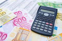 Euro banknotes and calculator. Filling taxes Royalty Free Stock Images
