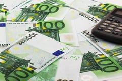 Euro banknotes and calculator. Several 100 Euro banknotes and a digital calculator Stock Images