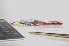 Euro banknotes, calculator and ballpen. On white background Stock Image