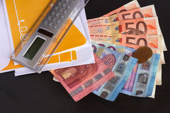 Euro banknotes, calculator and envelopes on a black background. royalty free stock photo
