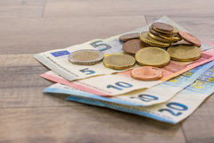 Euro banknotes and cents. On a wooden table Royalty Free Stock Photos