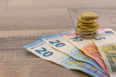 Euro banknotes and cents. On a wooden table Royalty Free Stock Photography