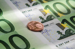 Euro banknotes and coin of one cent. 100 Euro banknotes and coin of one cent. Macro. Background Stock Photography