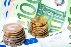 Euro banknotes and coins. Euro banknotes with various coins stock photo