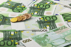 Euro banknotes and coins. Many 100 euro banknotes randomly placed and few euro coins stock photography