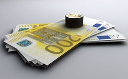 Euro banknotes and coins. A closeup of a stack of 200 Euro bills with a stack of Euro coins placed on them Royalty Free Stock Image