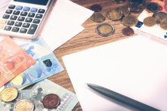 Euro banknotes and coins with bills to pay. Finances and budget. Concept Stock Image