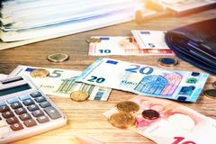 Euro banknotes and coins with bills to pay. Finances and budget. Concept Stock Photo