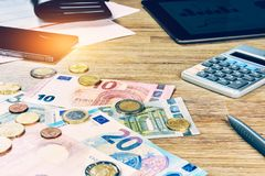 Euro banknotes and coins with bills to pay. Finances and budget. Concept Stock Images