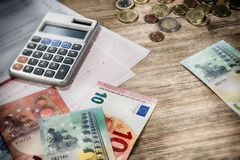 Euro banknotes and coins with bills to pay. Finances and budget. Concept Royalty Free Stock Photography